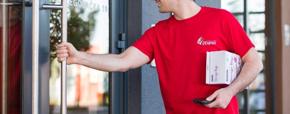 Kurir sa paketom i pda uredjajem u ruci, vrši dostavu i otvara vrata zgrade.