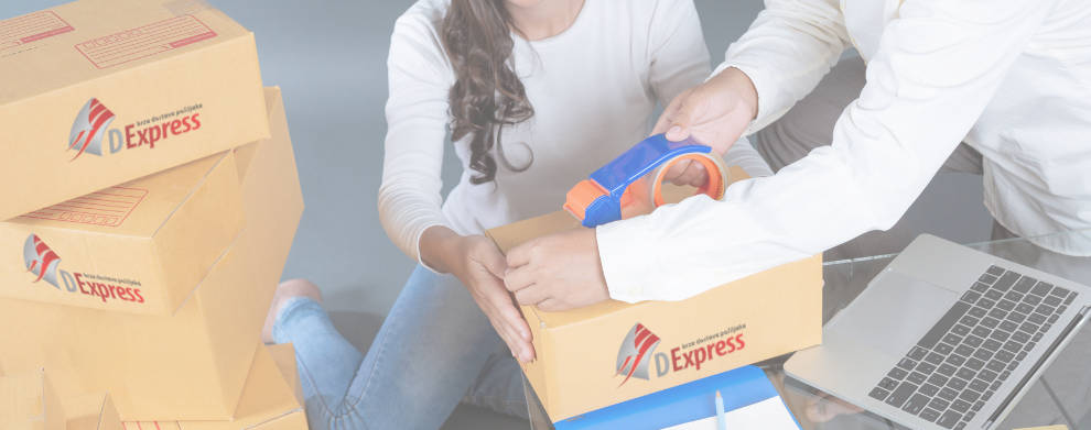 Dvoje ljudi pakuje ispravno pošiljke. Na stolu se nalaze paketi i laptop.