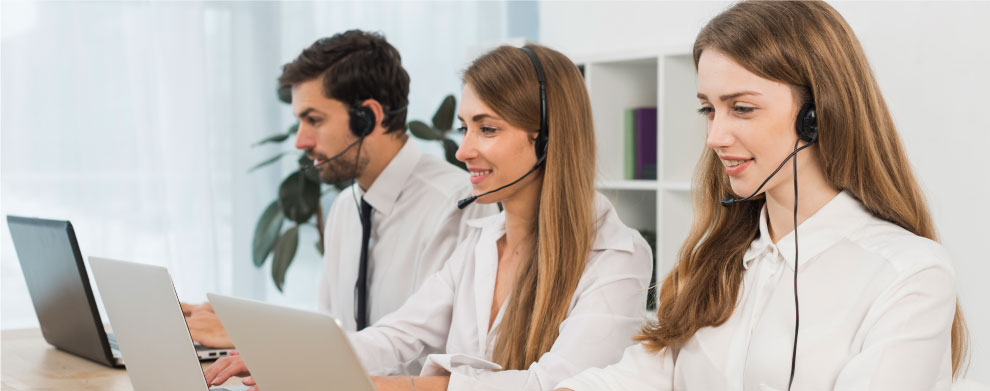 Zaposleni u call centru na radnom mestu, koji kjoriste lap top, slušalice i mikrofon.